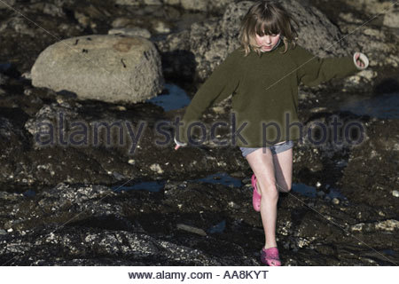 Girl jumping over rocks - Stock Photo