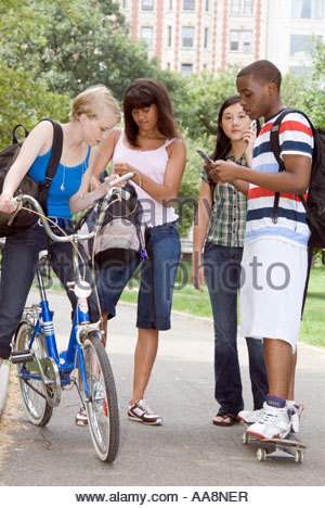 Group of teenagers using hand held devices outdoors - Stock Photo