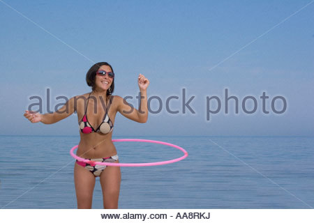 Young woman playing with hula-hoop on beach - Stock Photo