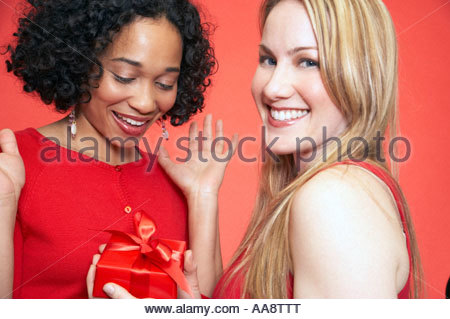 Woman giving gift to friend - Stock Photo