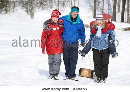 Family pulling sled up snowy hill - Stock Photo