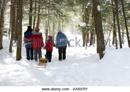 Family pulling sled behind them - Stock Photo
