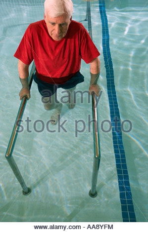 Man having physical therapy in pool - Stock Photo