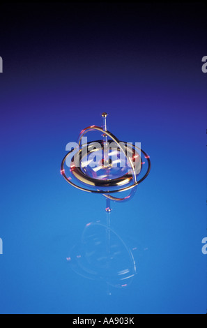 A gyroscope stay upright for a while while it spins On blue lit Plexiglas in studio - Stock Photo