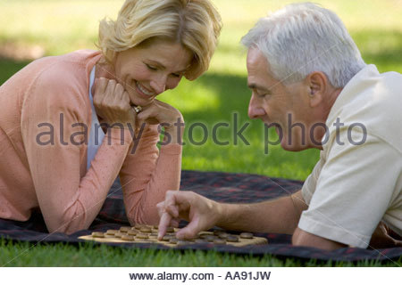 Senior couple playing checkers in park - Stock Photo