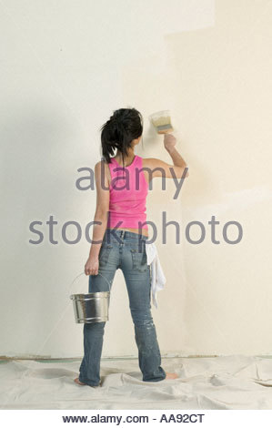 Woman painting unfinished room - Stock Photo