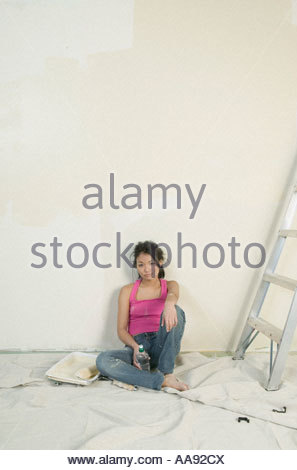 Asian woman resting while painting unfinished room - Stock Photo