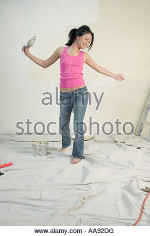 Asian woman dancing while painting unfinished room - Stock Photo