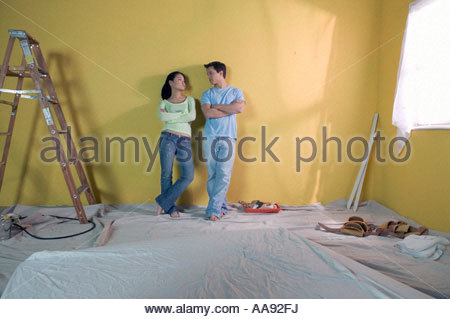 Asian couple leaning against freshly-painted wall - Stock Photo