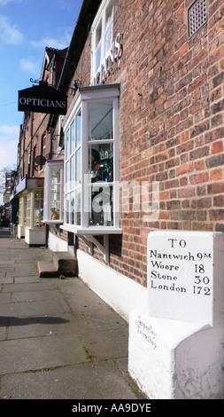 Shopfronts and milestone, Tarporley Cheshire England - Stock Photo