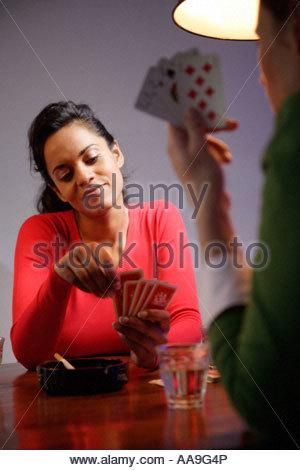 Hispanic women playing poker - Stock Photo