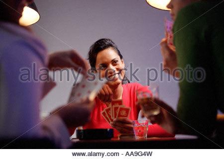 Hispanic women playing poker with friends - Stock Photo