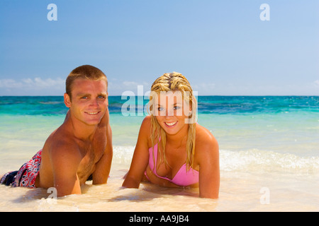 young couple lying on the sand at water s edge - Stock Photo