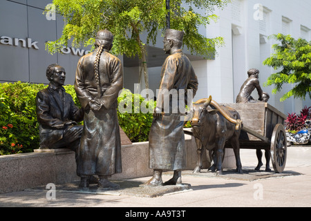 River Merchants bronze sculpture by Aw Tee Hong on riverbank Boat Quay Conservation Area Central Area Singapore - Stock Photo