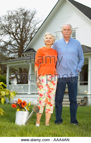 Senior couple standing in front of house - Stock Photo