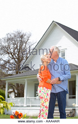 Senior couple embracing in front of house - Stock Photo