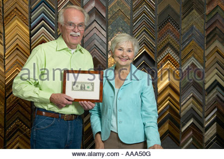 Senior couple holding first dollar in frame shop - Stock Photo