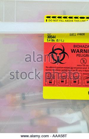 Biohazard Warning label on used syringes - Stock Photo