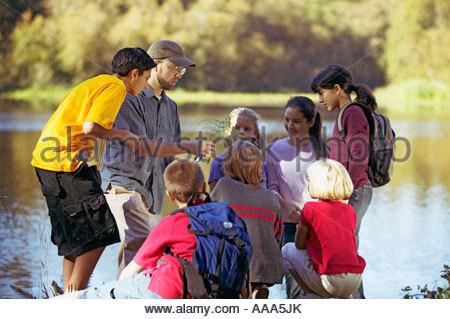 Students examining plants by lake - Stock Photo