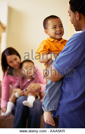 Asian parents holding children - Stock Photo