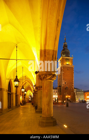 the Cloth Hall and City Hall Tower in the Main Market Square Rynek Glowny at dusk Krakow Cracow Poland - Stock Photo