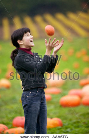 Young girl tossing pumpkin in air and catching it - Stock Photo
