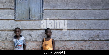 Two African boys against wooden wall in Accra, Ghana - Stock Photo