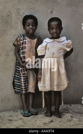 Two little African girls against a wall in Accra, Ghana - Stock Photo