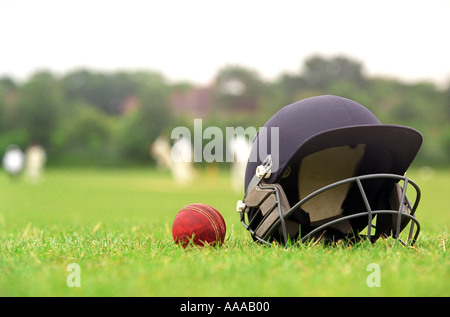 A cricket helmet and ball with a match taking place in the background - Stock Photo