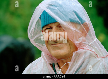 Bulgarian farmer wrapped  in a plastic sheet for protection against the rain - Stock Photo