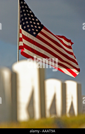 A United States flag flies over the headstones of military personnel at the National Cemetary in Santa Fe New Mexico - Stock Photo