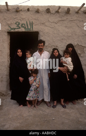 Marsh Arabs polygamy. Iraq portrait of a family man with three wives  their children standing outside their home. - Stock Photo
