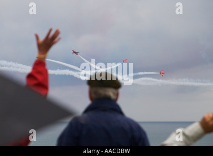 People watch Red Arrows flying display team one waving in excitement at Croyde Bay Devon England - Stock Photo