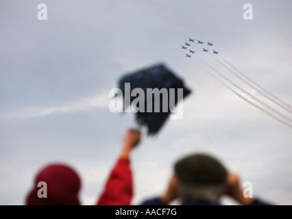 Couple watch Red Arrows flying display team fly past lady waving half folded rain brolly at Croyde Bay Devon England - Stock Photo