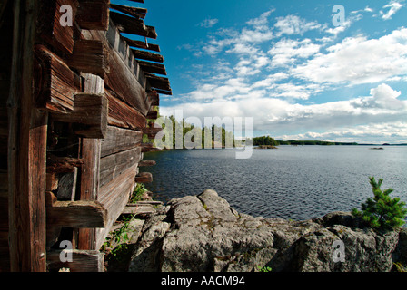 old wooden hut on rocks on the lakefront of a lake in Saimaa region in Finland - Stock Photo