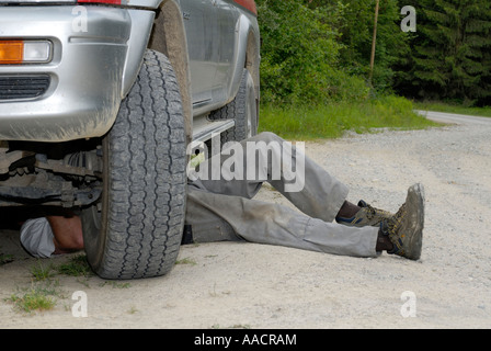 Man under a broke-down vehicle, Germany, Europe - Stock Photo