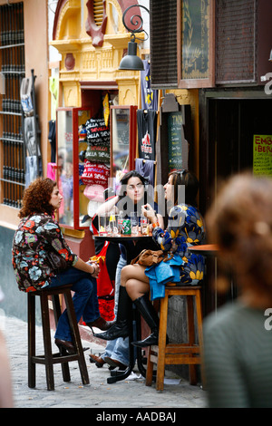 Three women sitting at a Bar Cafe in Barrio Santa Cruz Seville Spain - Stock Photo