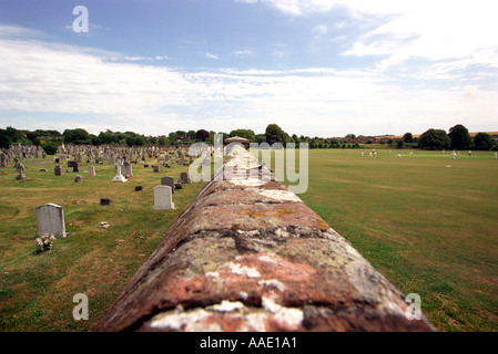 A cricket match taking place next to a graveyard - Stock Photo