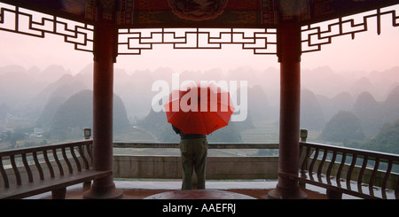 Girl with red umbrella in the pavilion, watching karst hills in mist, Thousand Peaks, Guizhou China - Stock Photo