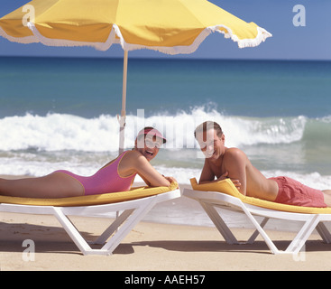 young couple sunbathing on loungers by the sea under sunshade - Stock Photo