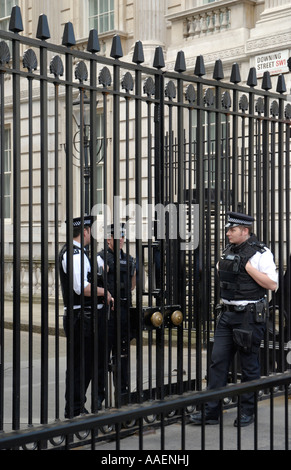 Three uniformed police guards, two inside, and one outside main gates to Downing Street, London, England, UK - Stock Photo