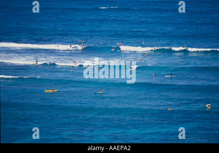 Surfers and kayakers catching waves off of Flat Island Kailua Bay Oahu Hawaii - Stock Photo