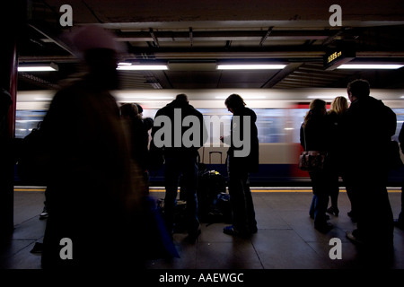 London Underground tube network with passengers on platform with train speeding past - Stock Photo