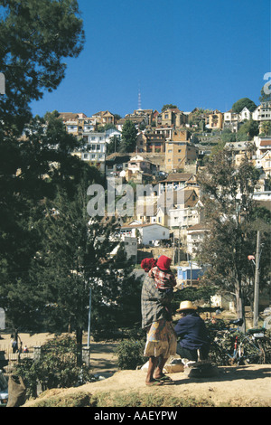 Local Malagasy family in front of typical housing on a steep hillside Antananarivo Madagascar - Stock Photo