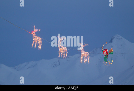 Santa & Reindeer lights strung across wire in front of snow covered peak Southcentral Alaska Winter - Stock Photo