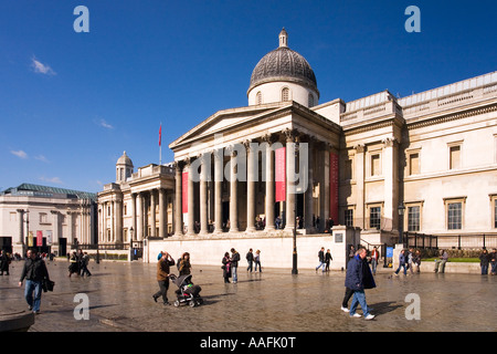 The National Gallery in spring sunshine and tourists in Trafalgar Square London - Stock Photo