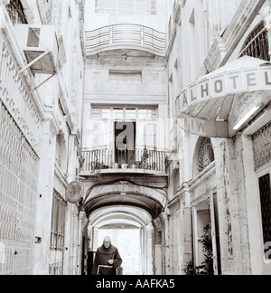 Travel Photography - A monk strolls through an arcade in the Armenian quarter of Jerusalem in Israel in Middle East. Street Scene Reportage People