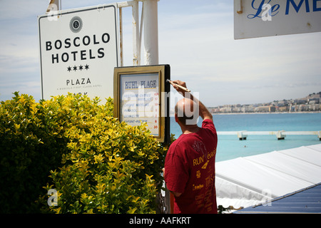 Sign maintenance on a hotel's private beach and restaurant in expectation of the tourists rush in the high season, - Stock Photo