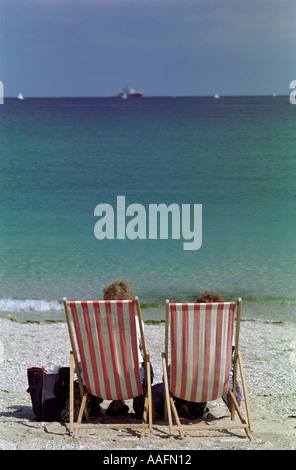 people sitting on a deckchair looking out to sea - Stock Photo