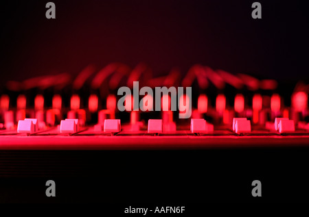A recording desk in a recording studio with red light - Stock Photo